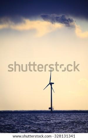 wind turbines power generator farm for renewable energy production along coast baltic sea near Denmark at sunset or sunrise. Alternative green energy ecology. - stock photo