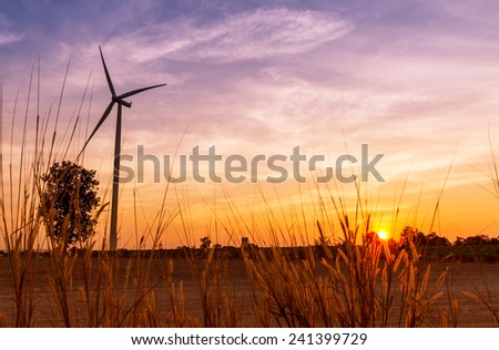 Wind turbines power generator on sunset at farmer field - stock photo