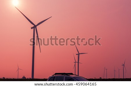 Wind turbines power generator with car on sunrise at farmer field