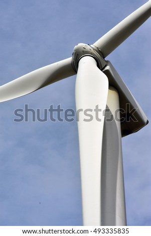 Wind turbines producing electricity on the prairie, blades are blurred some from movement.