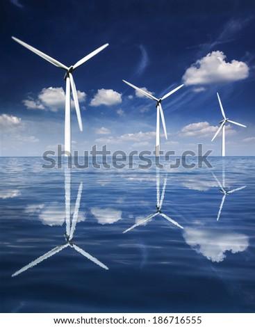 Wind turbines reflected in calm seas - stock photo