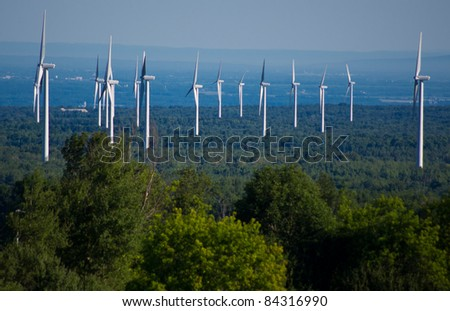 Wind turbines rising above the forest - stock photo