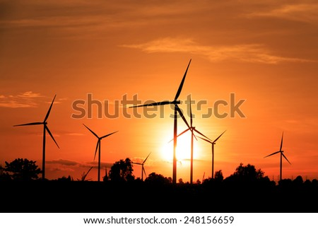 Wind turbines silhouette at sunset - stock photo