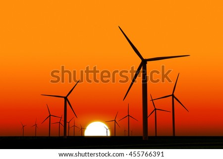 wind turbines silhouettes at dusk with sun in background - stock photo