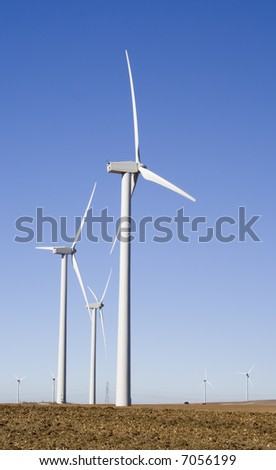 Wind turbines standing in a field in central Spain.