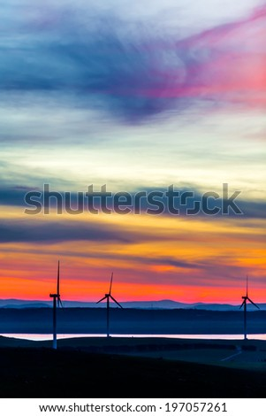 Wind turbines standing on the hills near the water shore in the dusk twilight - stock photo