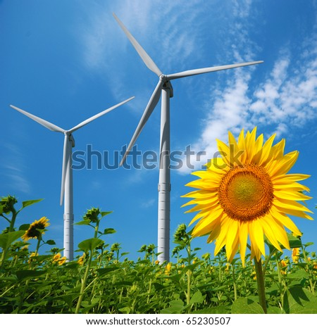 Wind turbines under blue cloudy sky - stock photo