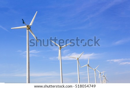 Wind turbines with a blue sky with clouds.