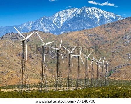 Wind turbines with a scenic snow-capped mountain in the background and a clear blue sky - stock photo