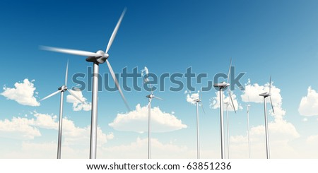 Wind turbines with blue sky and clouds in the background.