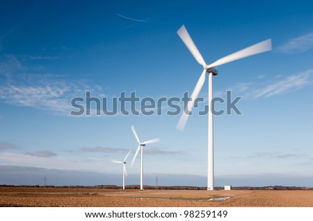 Wind turbines with motion blur / Wind farm showing motion blur on rotating blades - stock photo