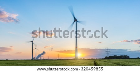 Wind turbines with power plant at sunset with cloudy sky