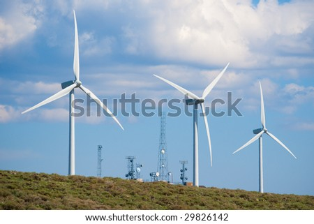 Wind turbines with radio telecommunications towers in background