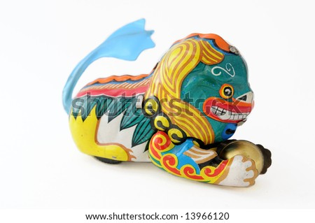 Wind-up toy dragon from China with blue tail and a golden ball in its paws, made of brightly-painted metal.