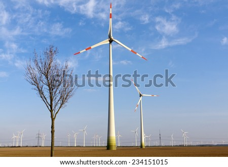 Wind Wheel (windmills) and a tree. In background stand electricity pylons on the field. - stock photo
