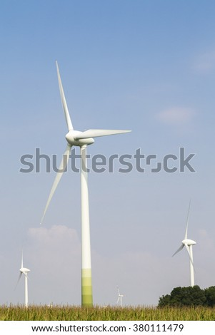 wind wheels on blue sky with cornfield - stock photo