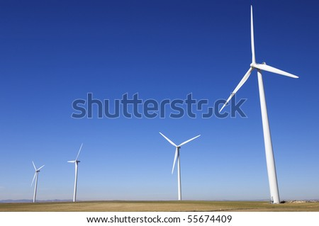 windfarm fied with blue and clear sky - stock photo