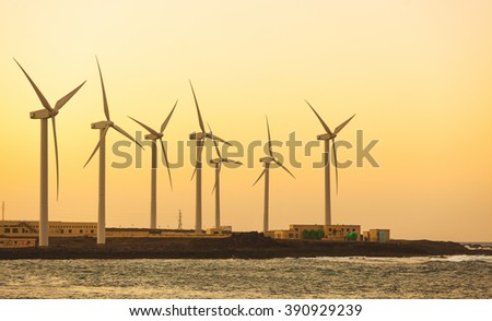 Windfarm view next to the seaside in Fuerteventura, Spain, at sunset. Wind turbines are used to power the desalination plant. Technology and ecology concepts.