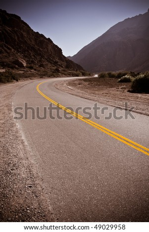 Winding desert road in Argentina, South America with bold Yellow lines in centre - stock photo