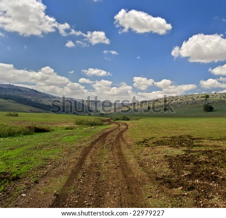 winding dirt road and cloudscpe