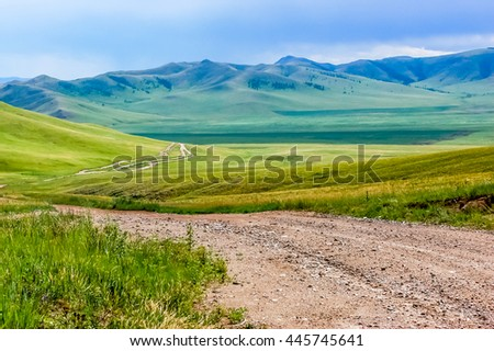 Winding dirt track through lush rolling hills of central Mongolian steppe - stock photo
