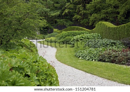 Winding path in a formal garden - stock photo