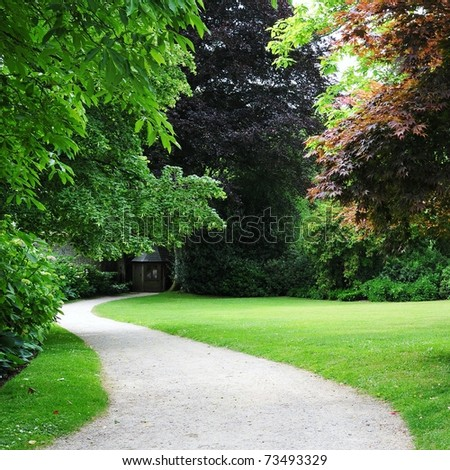 Winding Path through a Tranquil Verdant Garden - stock photo