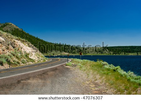 winding road by lake - stock photo