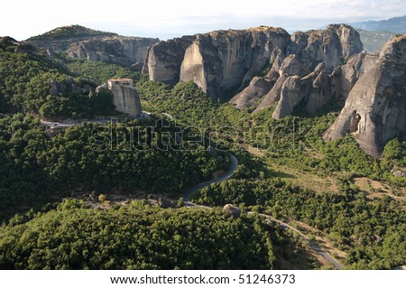 winding road crosses the landscape of the Meteora to go to the Roussanou monastery - stock photo