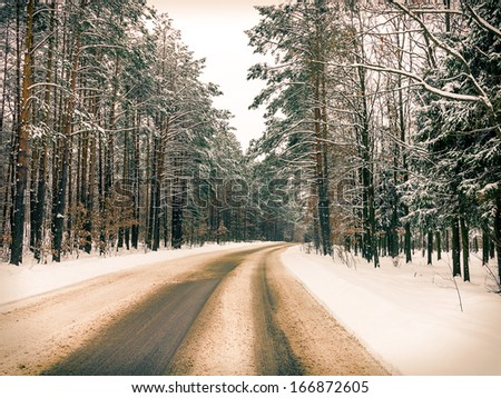 Winding road hidden behind tall pine trees, frosty winter landscape. Effect of an old photo toning - stock photo