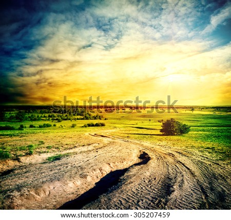 Winding road in a sandy field under dramatic sky - stock photo