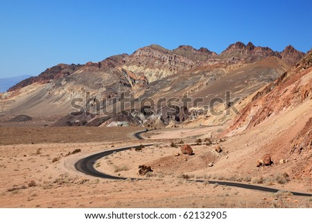 Winding road in Death Valley. Dry clay soil and a cloudless sky - stock photo