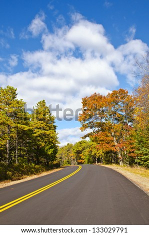 Winding road in New England on a sunny autumn day