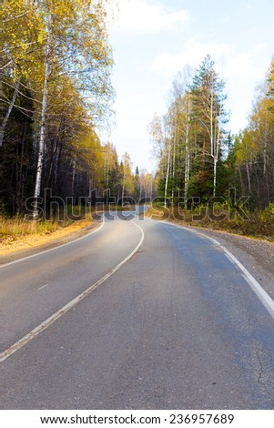 Winding road in the autumn forest - stock photo