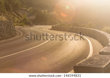 winding road in the sunrise - stock photo