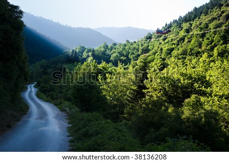 winding road in the valley after the rain at twilight - stock photo