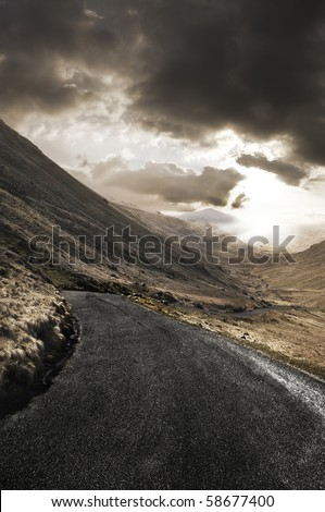 Winding road leading through a beautiful rugged landscape. - stock photo