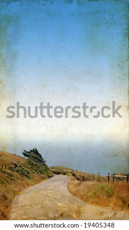 Winding road leading to the ocean on grunge background. Lots of copy-space for your text. - stock photo