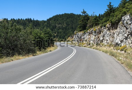 winding road mountain crosses fir woods under the blue clear sky - stock photo