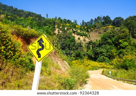 winding road sign in yellow and black on blue sky background on a country road  ,Thailand - stock photo