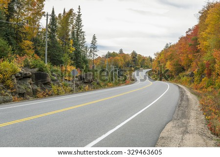 Winding Road Surrounded by Fall Color - Algonquin Provincial Park, Ontario, Canada   - stock photo