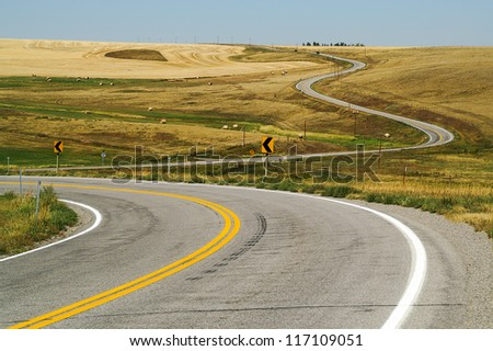 Winding road through big sky country in rural Montana. - stock photo
