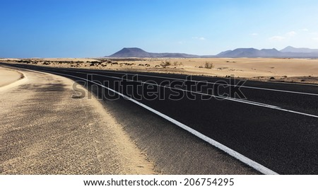 Winding road through the dunes of Corralejo desert with volcano in the background, in Fuerteventura, Canary Islands, Spain. - stock photo