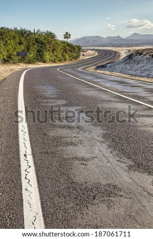 Winding road through the dunes of Corralejo with volcanoes in the background, in Fuerteventura, Canary Islands, Spain. - stock photo