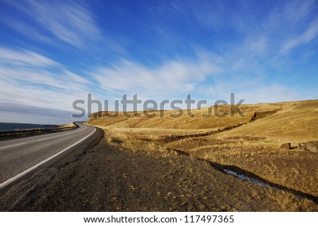 Winding Rural Road with No Cars Single lane, paved road winding through rural hills on a sunny day with bright blue skies and smooth clouds. The road is empty. Setting: Icelandic Ring Road. - stock photo