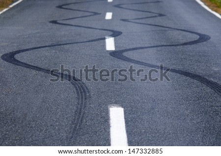 Winding skid marks of a vehicle on a street road. - stock photo