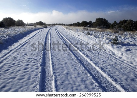 Winding small road covered with snow - stock photo