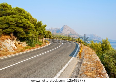 Winding Tarmac Road above blue sea