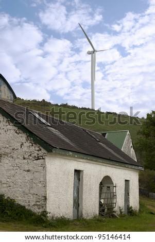 windmill above abandoned farm on lush irish countryside landscape in glenough county tipperary ireland - stock photo