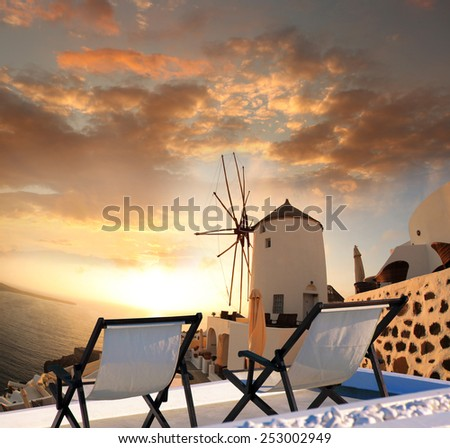 Windmill against colorful sunset in Santorini, Greece - stock photo